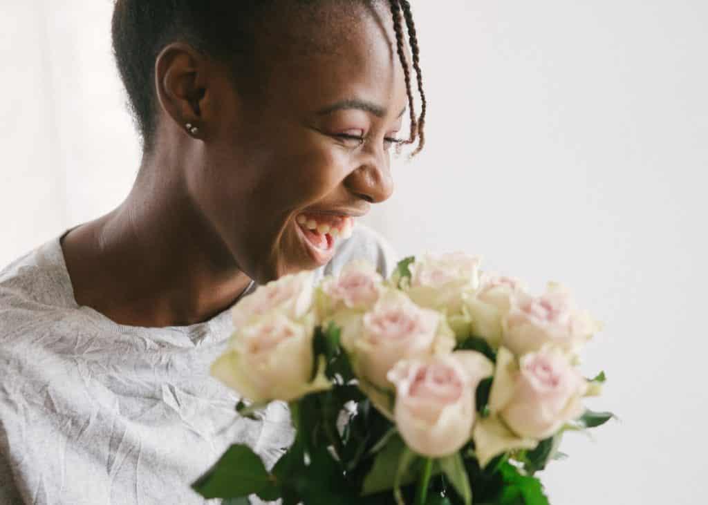 Mulher sorrindo com um buquê de rosas em sua frente