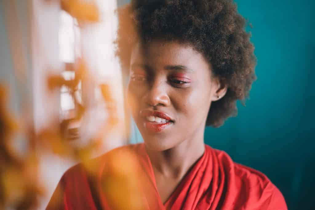 Mulher sorrindo olhando apra baixo ao lado de uma cortina