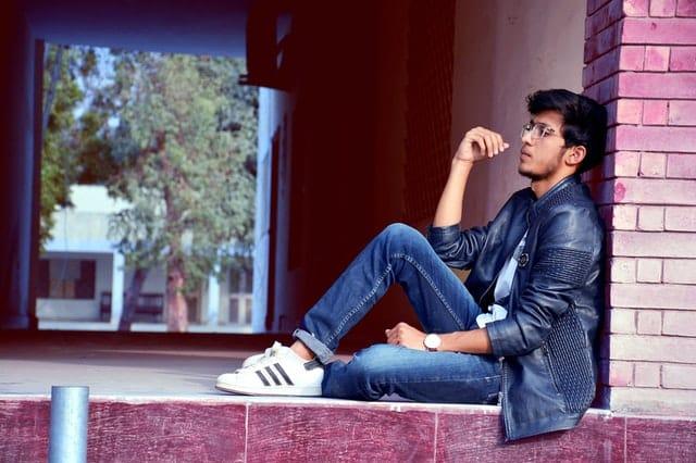 Homem sentado com expressão pensativa de perfil apoiado em pilastra