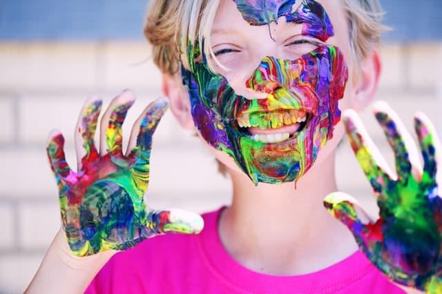 Menino com tintas misturadas no rosto e nas mãos sorrindo