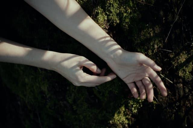 Mãos de mulher em contato com a grama