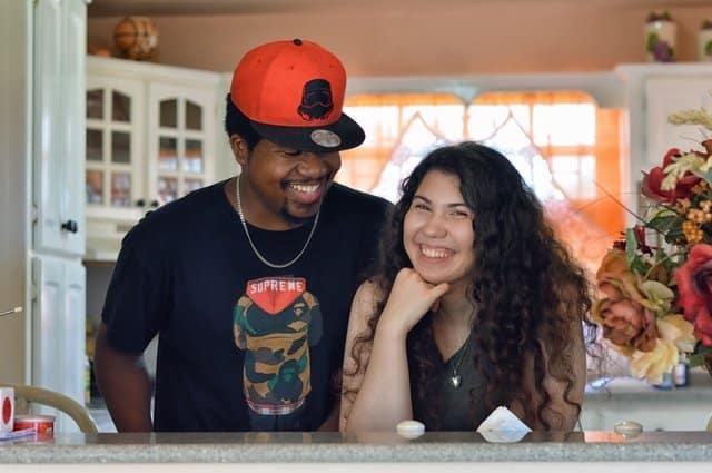 Casal em pé em cozinha sorrindo