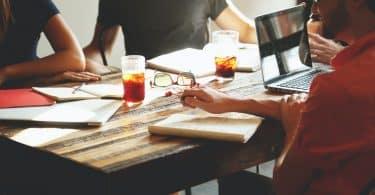 Pessoas reunidas na mesa com copos de chá, cadernos e notebook