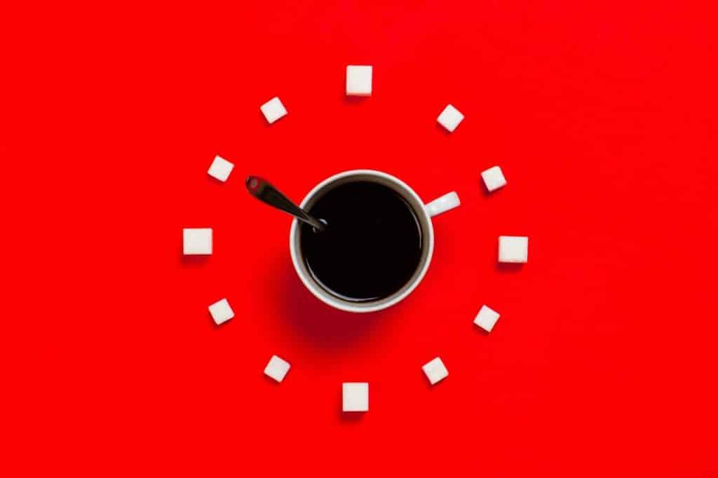 Xícara de café branca com colher de metal dentro, cubos de açúcar ao redor.