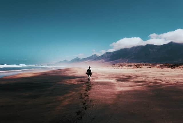 Pessoa caminhando em praia com montanha céu e nuvens ao fundo