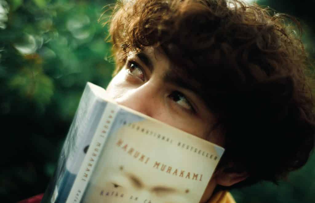 Pessoa segurando um livro em frente ao seu nariz e boca, deixando apenas os olhos