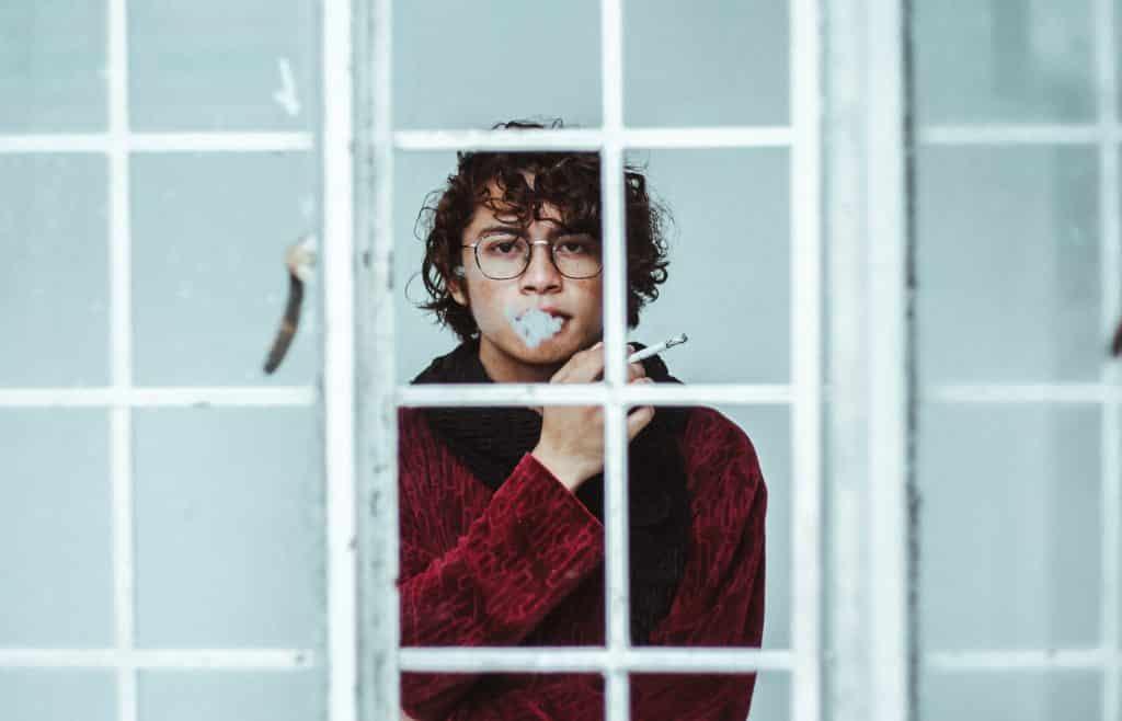 Homem fumando cigarro na janela
