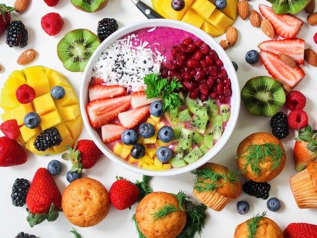 Mesa branca com frutas e bolinhos ao redor, com tigela branca ao meio.