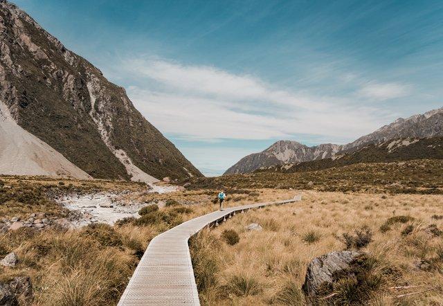 Homem andando em ponte no deserto com montanhas ao fundo