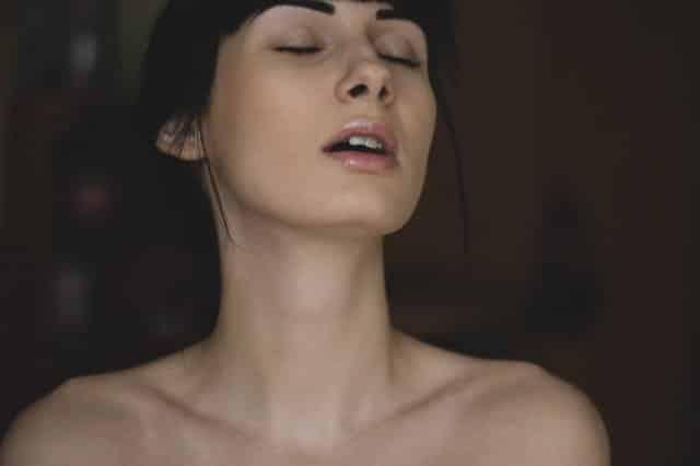 Mulher com expressão de prazer de olhos fechados