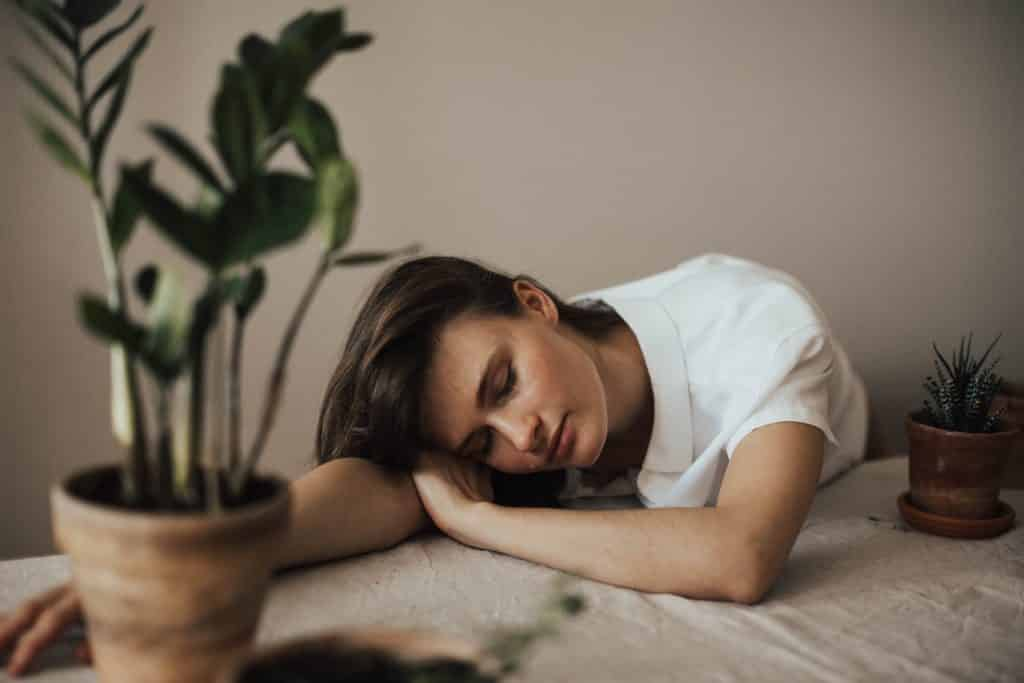 Mulher deitada na mesa ao lado de um vaso