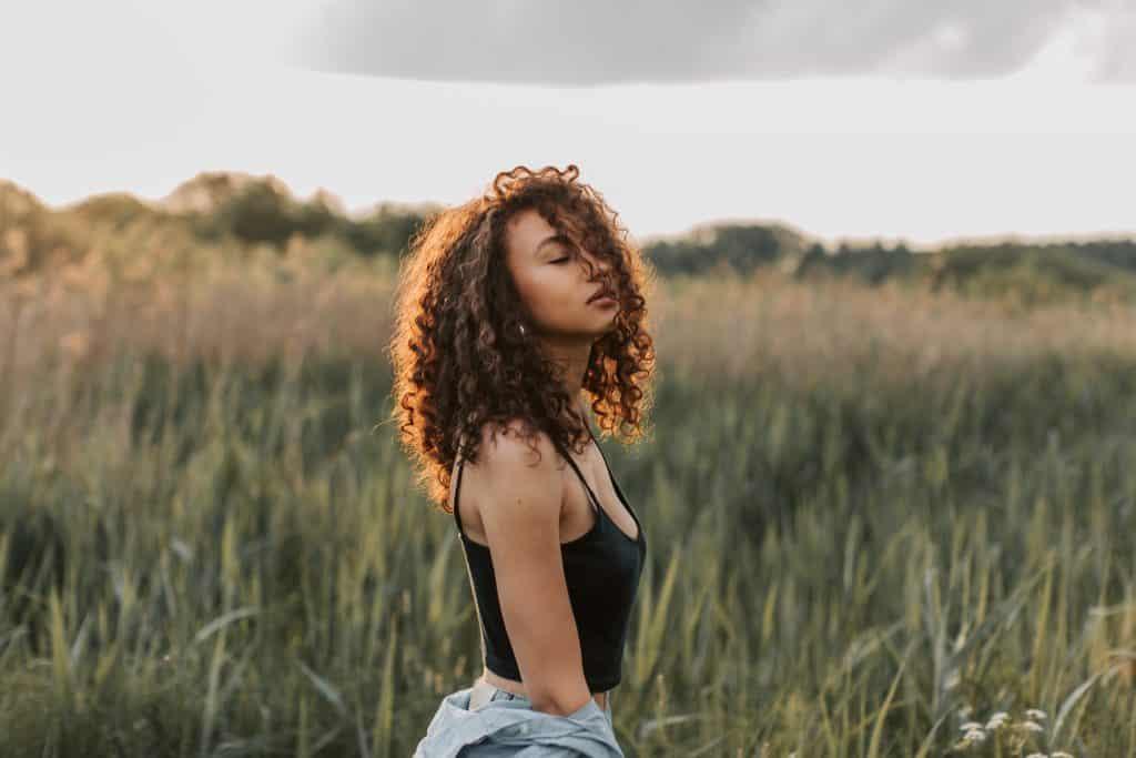 Mulher em um campo de gramado de olhos fechados e cabelo no rosto