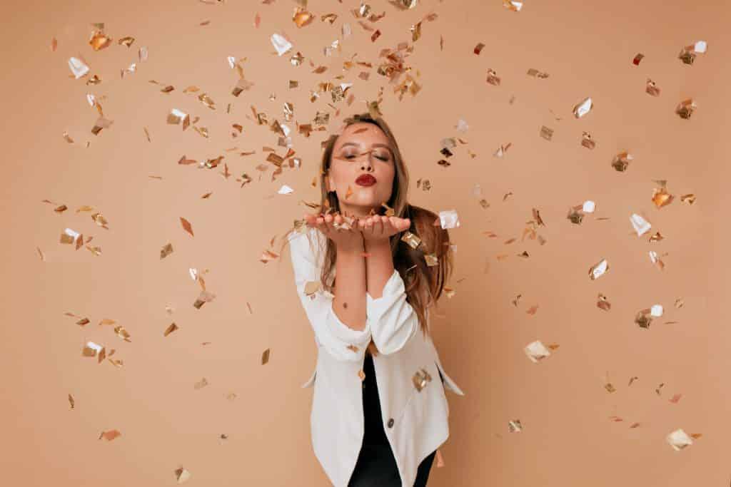 Mulher em pé fazendo bico de olhos fechados com papéis dourados espalhados no ar