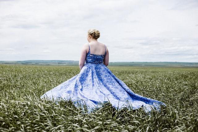 Mulher de costas em campo com vestido azul