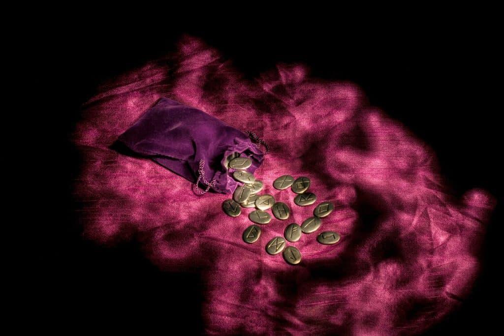 Imagem com fundo roxo trazendo as pedras das runas dispostas sobre um tecido aveludado também na cor roxa.