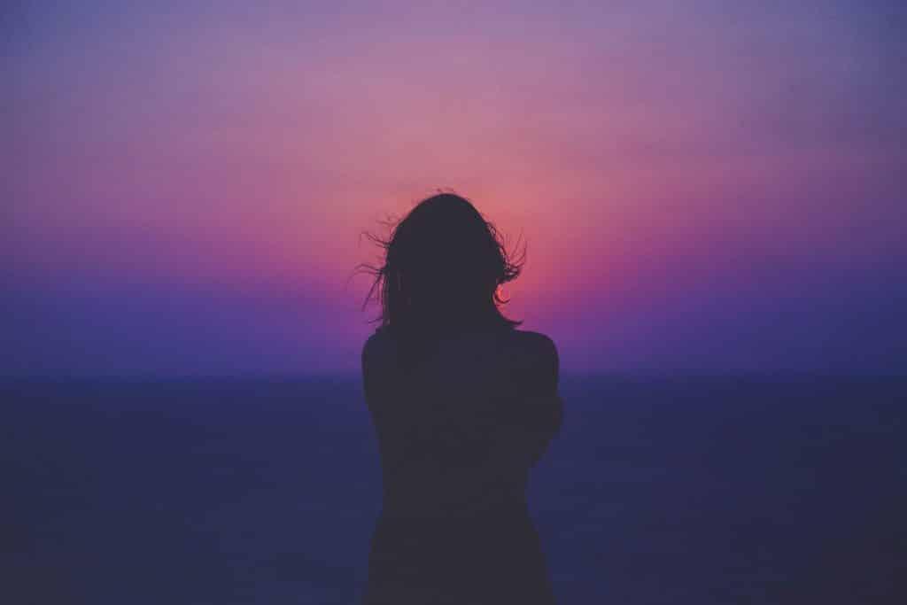 Silhueta de mulher olhando o pôr-do-sol.