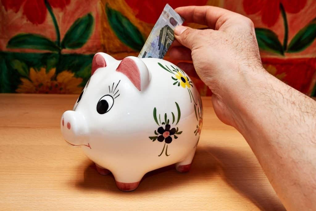 Imagem de um cofrinho de porcelana na cor branca feito em formato de um porquinho pintado à mão. A mão de um homem está ao fundo e ele está colocando uma cédula no cofrinho.