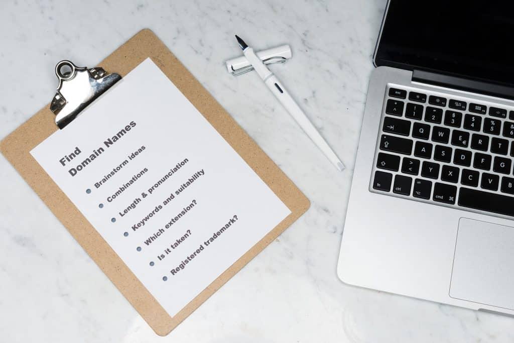 Imagem de uma prancheta com um papel branco onde estão anotadas diversas palavras. Ao lado uma caneta e um notebook. Trata-se de um exercício para ajudar na criatividade.