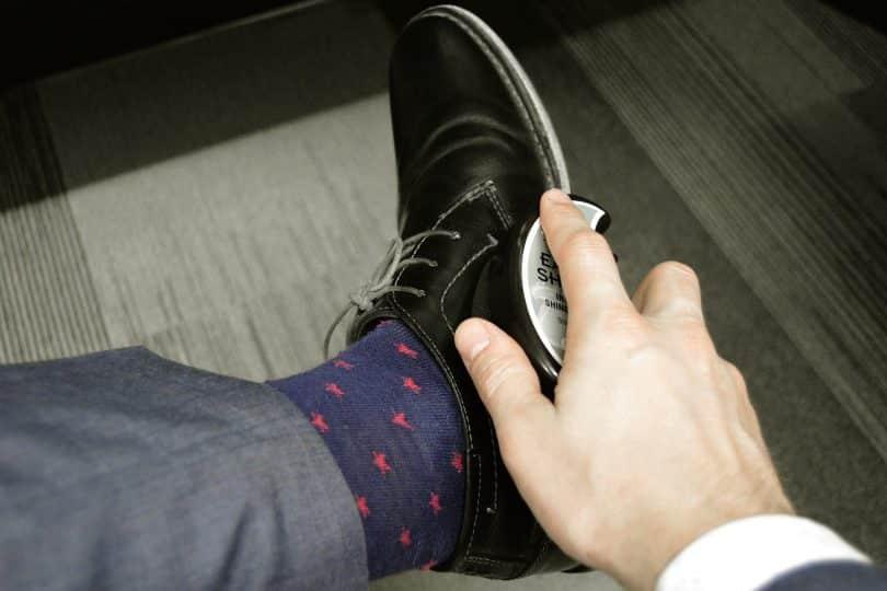 Imagem de um homem lustrando o seu sapato preto. Ele usa terno cinza e está se autocuidando.