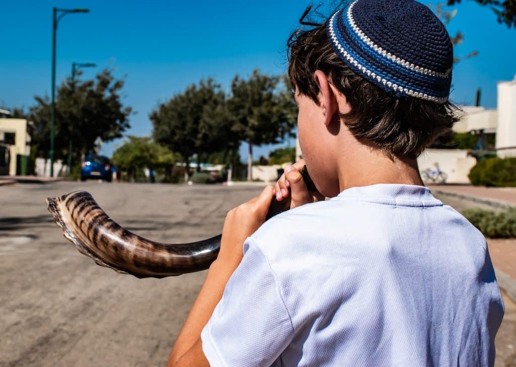 Imagem de uma criança judaíca tocando o shofar, um instrumento de sopro muito antigo feito de chifre de carneiro.