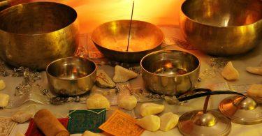 Imagem de vários elementos e itens para a prática do esoterismo. São vários tipos de bowls, incensos, pedras, velas, dispostos sobre uma mesa forrada com uma toalha branca.