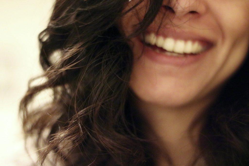 Imagem de um lindo sorriso de uma mulher de cabelos escuros, longos e ondulados.