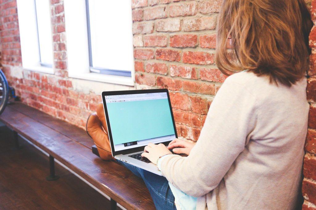 Imagem de uma adolescente estudando em seu notebook. Ela está sentanda em um banco de madeira em uma sala feita com parede de tijolinho vermelho.