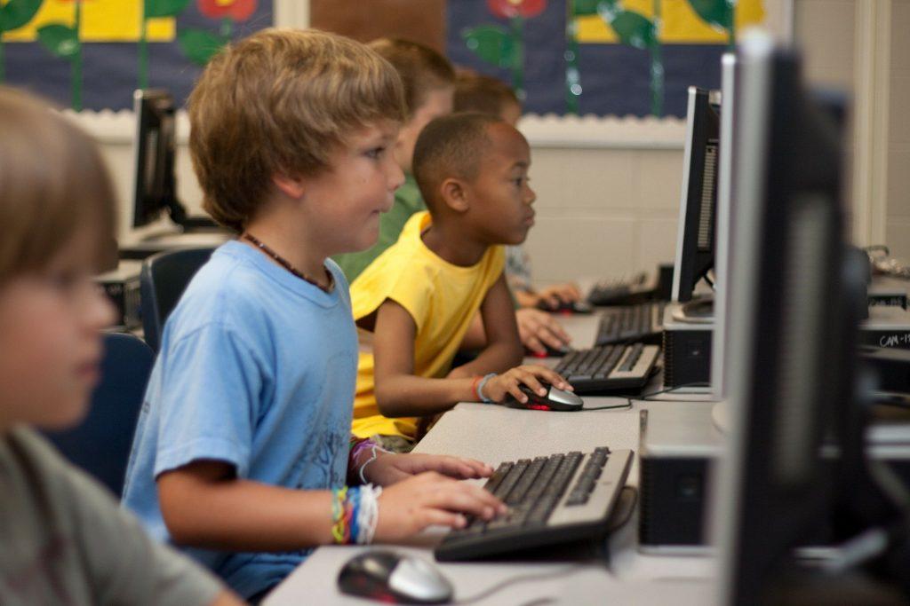 Imagem de uma sala cheia de crianças e com vários computadores. Muitas delas estão mexendo no computador.