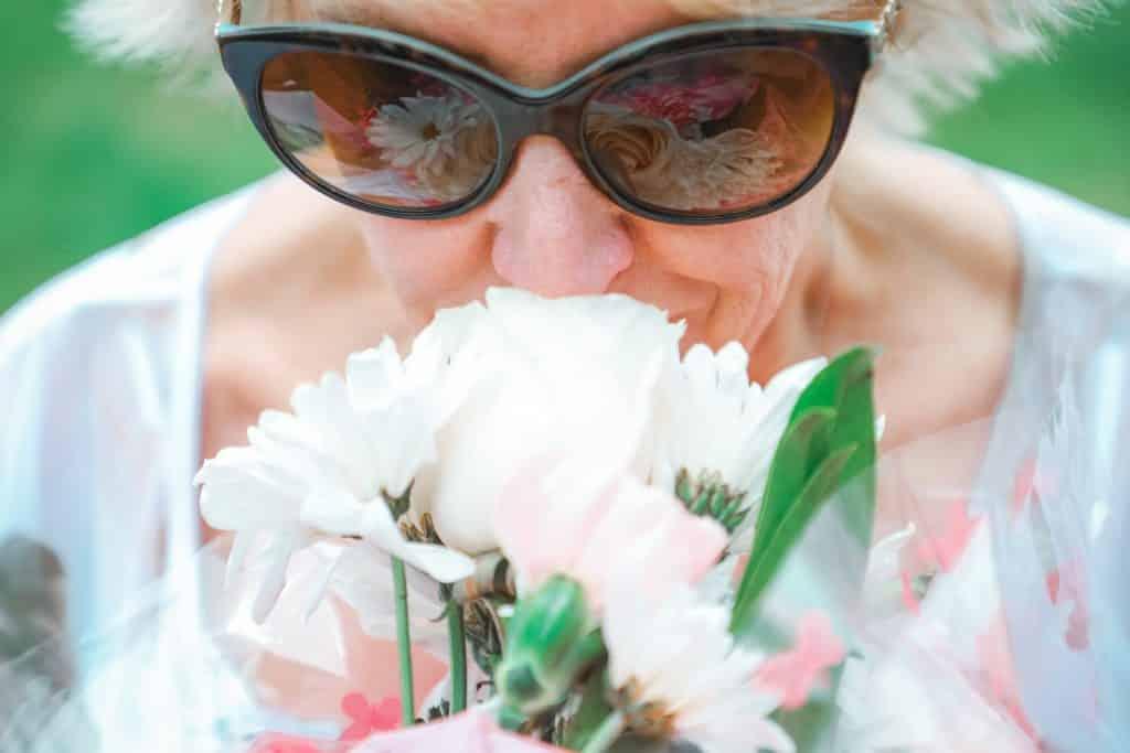 Idosa branca cheirando buquê de flores.