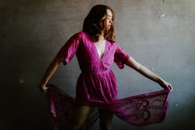 Mulher usando vestido roxo segurando na barra olhando para baixo