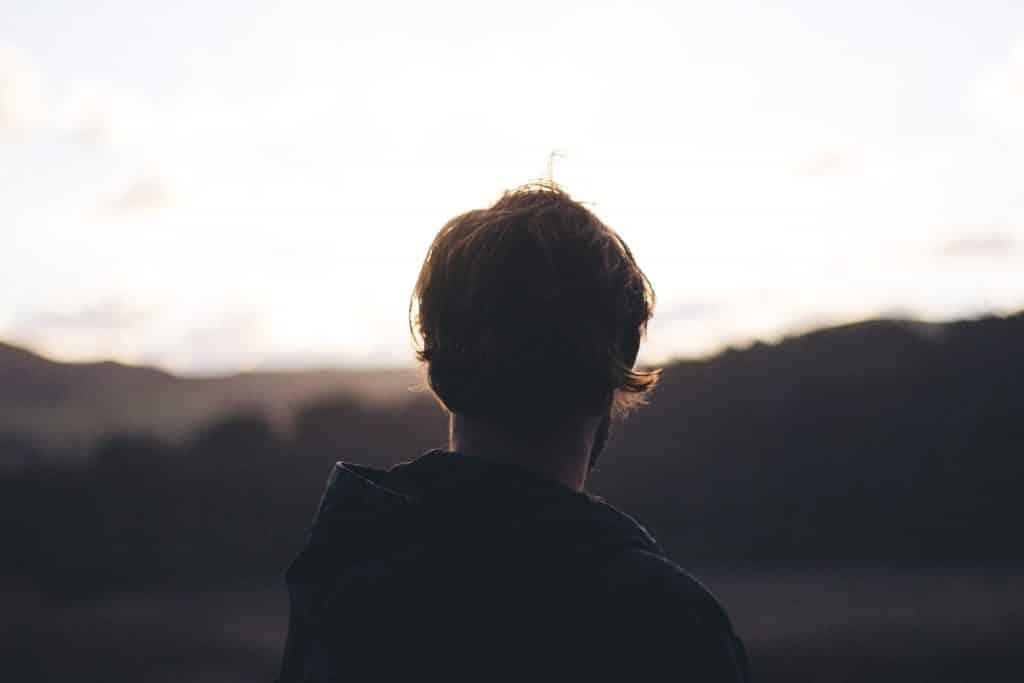 Homem olhando para montanhas a sua frente
