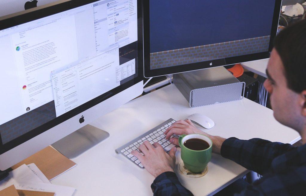 Imagem de um homem digitando. À sua frante uma caneca de café. Ele está trabalhando e usando duas telas para realizar as suas tarefas.