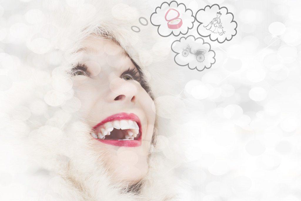 Imagem do rosto de uma mulher sorrindo. Ela está olhando para várias nuvens de pensamentos que estão sobre a sua cabeça. Ela está sorrindo com as ideias criativas que estão sendo inspiradas por ela.