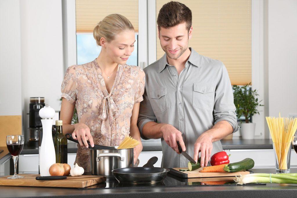 Mulher cozinhando ao lado do marido, ensinando ele a fazer um delicioso jantar. Ela está cozinhando uma massa de macarrão e ele cortando os legumes para uma bela salada.