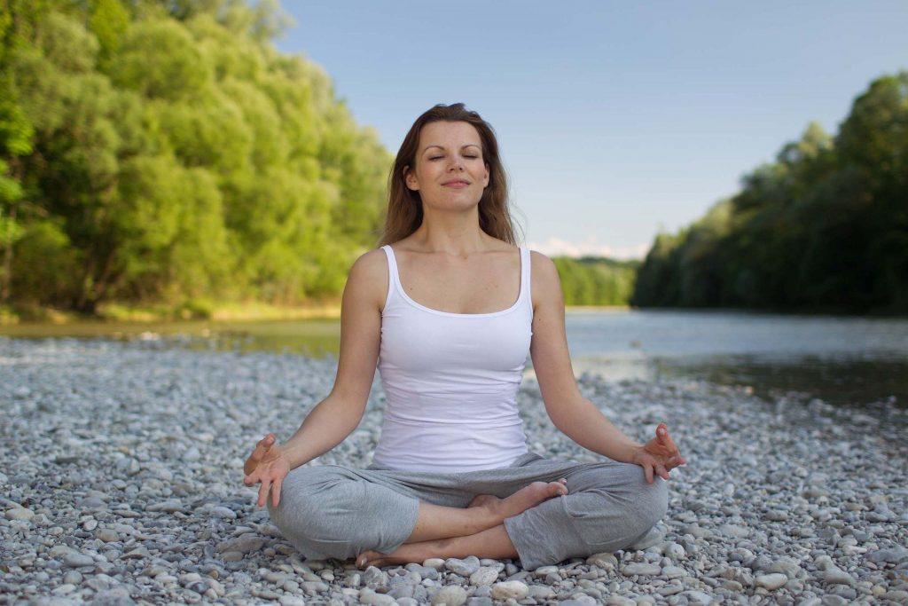 Imagem de uma mulher sentada em posição de yoga. Ela usa uma camiseta regata branca e uma calça cinza de moletom.