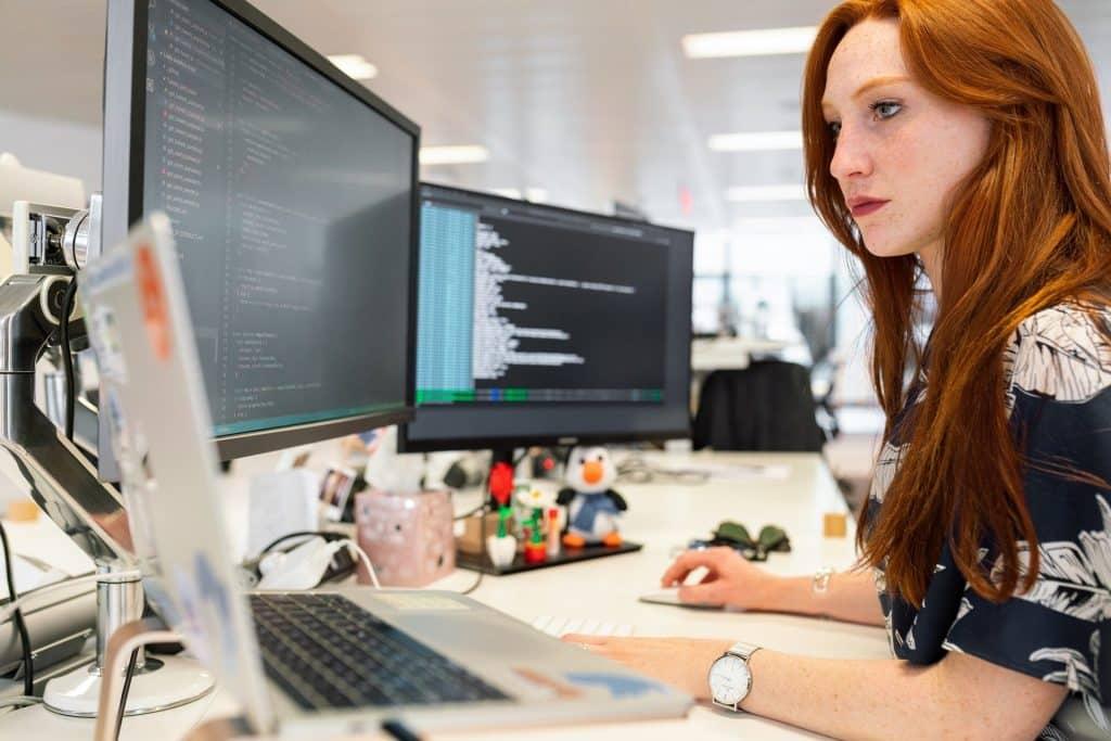 Imagem de uma mulher ruiva com cabelos longos. Ela está trabalhando sentada à frente de três computadores.