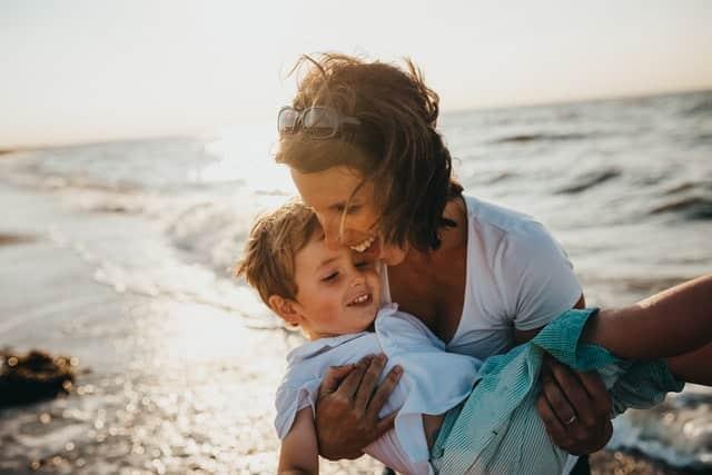 Mãe com filho nos braços com mar ao fundo
