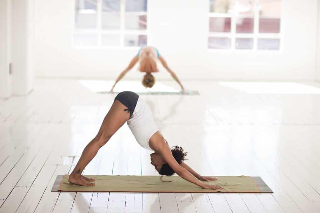 Imagem de uma sala ampla e branca e dentro dela duas mulheres praticam yoga.