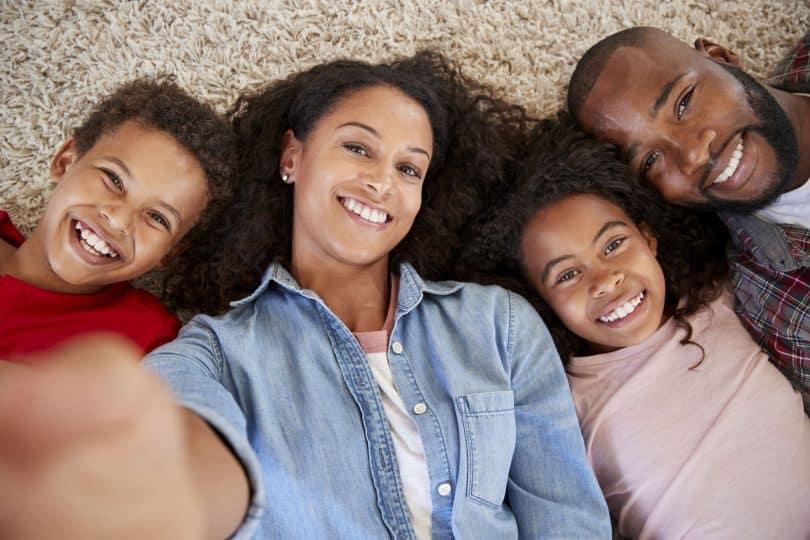 Família composta por crianças e adultos deitada sobre tapete. Mulher adulta fotografa a si mesma com os familiares.