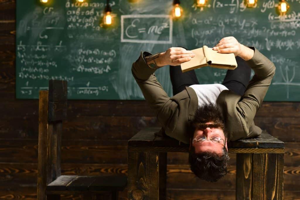 Homem deitado em cima de uma mesa lendo um livro enquanto no quadro negro ao fundo está todo escrito