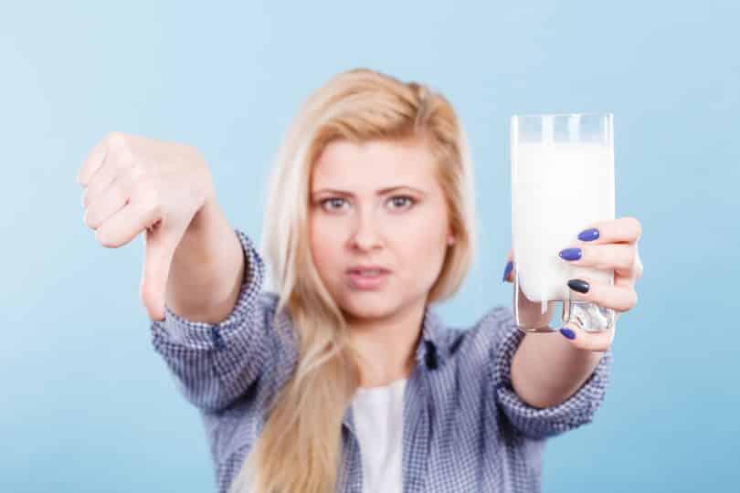 Mulher branca e loira segurando um copo de leite com uma mão, e com o polegar da outra para baixo.