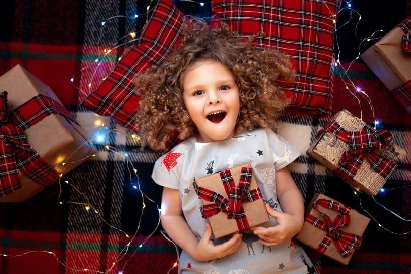 Menina branca deitada no chão rodeada de presentes.