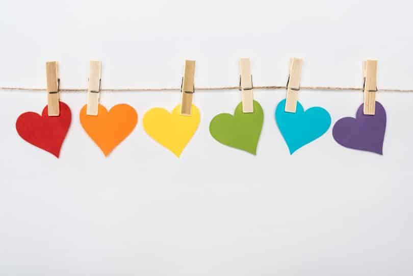 Imagem de vários corações feitos de papel e todos coloridos com as cores do conceito LGBT. Eles estão pendurados em um varal de corda.