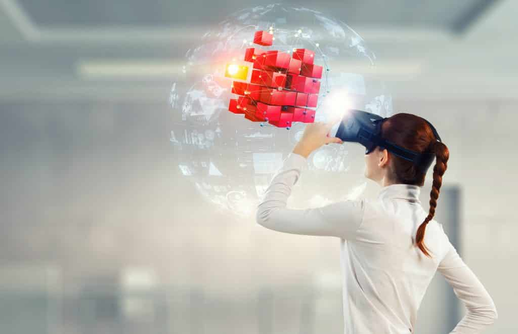 Imagem de uma jovem mulher usando um óculos 3D. Ela está olhando para um cubo vermelho centralizado dentro de uma bolha transparente.