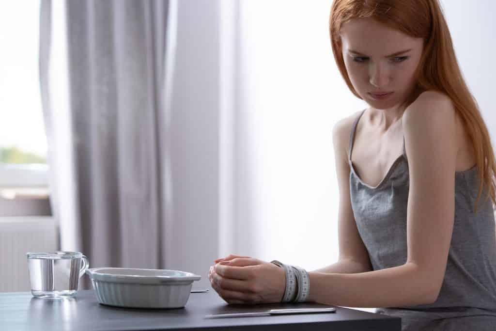 Imagem de uma jovem mulher que sofre de anorexia. Ela veste uma regata cinza. Esta sentada à frente de uma mesa e suas mãos estão amarradas com uma fita métrica.