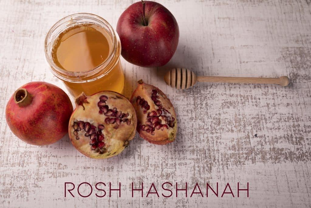 Imagem de frutas como romã e maçã, um copo de mel e o seu dosador, elementos que compõem a celebração do ano novo judaico. À frente dos ingredientes está escrito a palavra: Rosh HaShaná