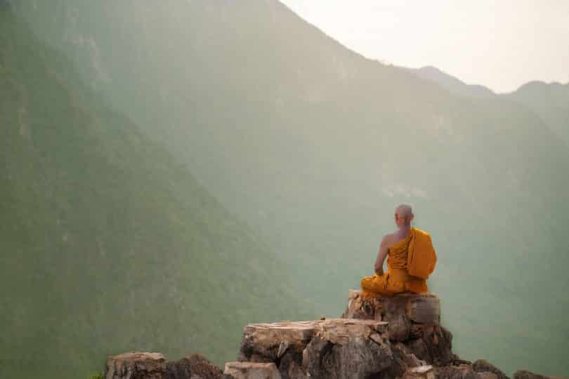 Monge com roupas laranjas sentado numa pedra enquanto observa paisagem.