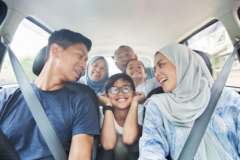 Família asiática dentro de um carro.