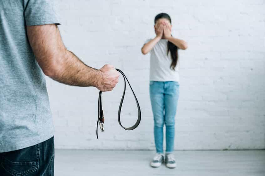 Pai com cinto na mão e garota em pé com mãos no rosto com medo