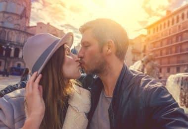 Casal tirando um selfie enquanto se beija